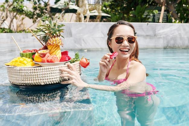 Femme appréciant de savoureux fruits de la passion rouge