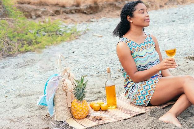 Femme appréciant un verre de vin sur la plage le matin