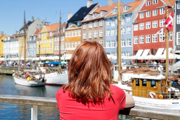 Femme appréciant la vue panoramique sur la jetée de nyhavn.