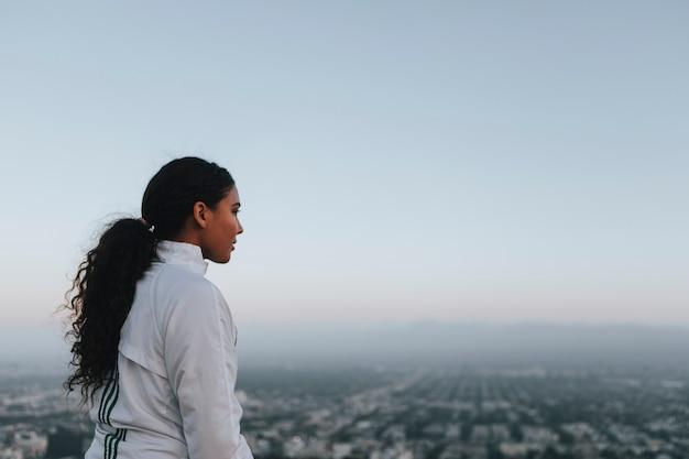 Femme appréciant la vue sur la ville depuis une colline