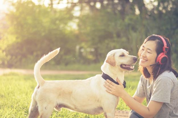 Femme apprécier écouter de la musique par le casque en plein air et en jouant avec un chien amical au coucher du soleil