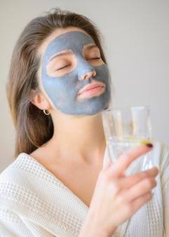 Femme, apprécier, spa, chez soi, à, masque facial, et, eau