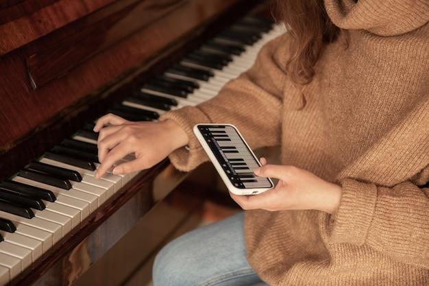Une femme apprend à jouer du piano à l'aide d'une application sur son téléphone