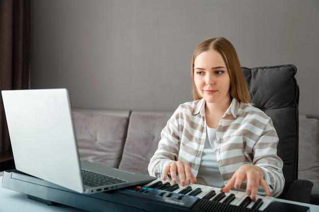 Une femme apprend à jouer du piano en ligne à l'aide d'un ordinateur portable à l'intérieur de la maison. cours en ligne de piano synthétiseur