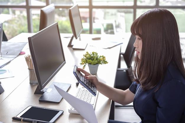 La femme appuie sur la calculatrice au bureau