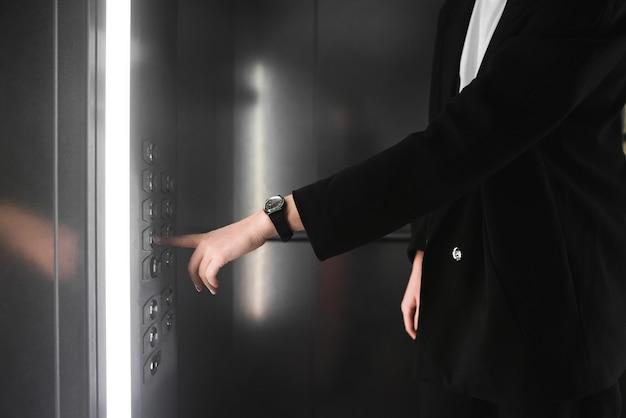Femme en appuyant sur le bouton de l'ascenseur.
