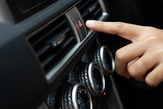 Femme appuyant sur les lumières d'urgence à l'intérieur de sa voiture