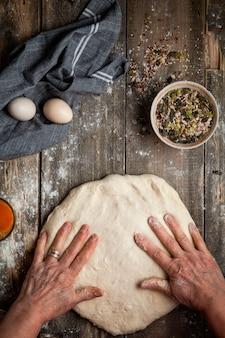 Femme en appuyant sur la pâte avec les mains sur la vue de dessus de table en bois.