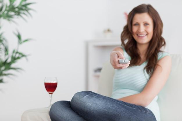 Femme en appuyant sur une télécommande tout en étant assis sur un canapé