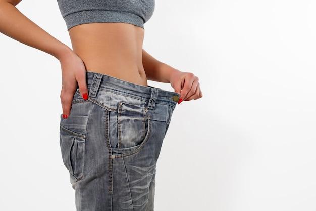 Femme après avoir perdu du poids dans de vieux gros jeans. isolé sur fond blanc.