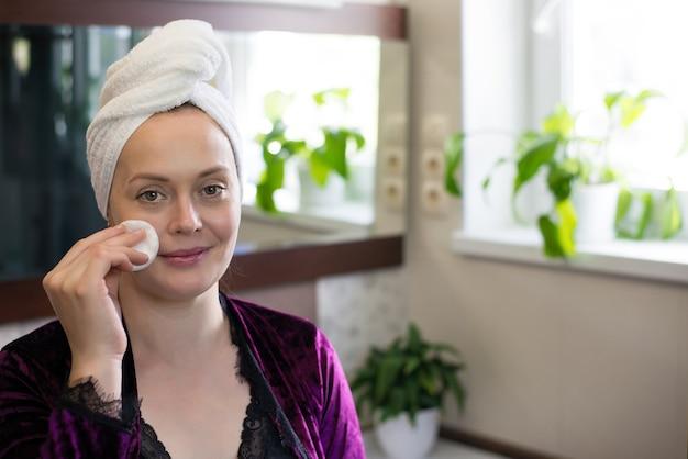 Une femme après un bain fait des soins de la peau du visage à domicile