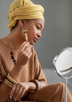 Femme arabe à l'aide d'un masseur facial. traitement de beauté