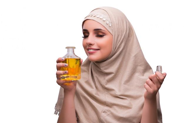 Femme arabe avec une bouteille de parfum isolé sur blanc