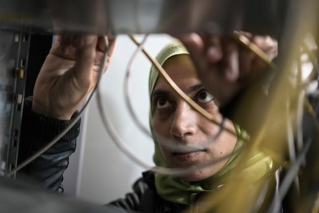 Femme arabe dans la salle des serveurs, câbles de commutation