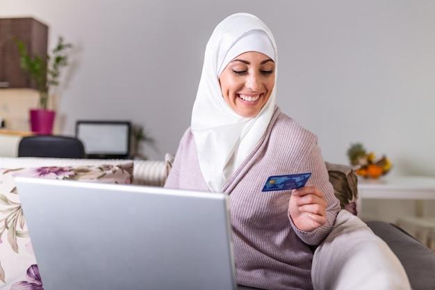 Femme arabe faisant un achat en ligne sur un ordinateur portable. paiement par carte de crédit. achats en ligne femme musulmane