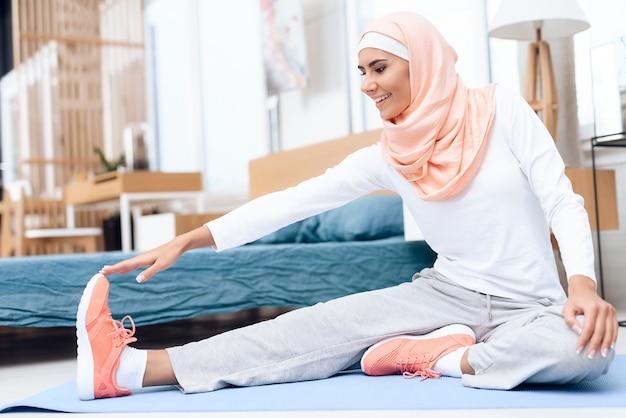Femme arabe faisant de la gymnastique dans la chambre à coucher.
