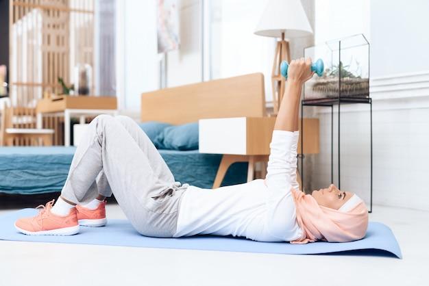 Femme arabe faisant de la gymnastique dans la chambre