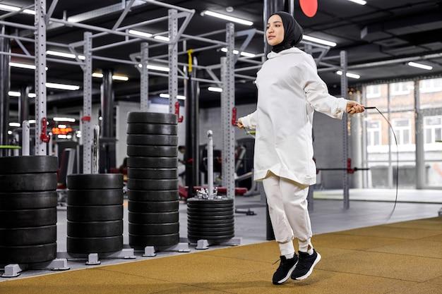Femme arabe en formation de hijab avec corde à sauter, mince femme forte engagée dans le sport, au gymnase moderne, concept de remise en forme