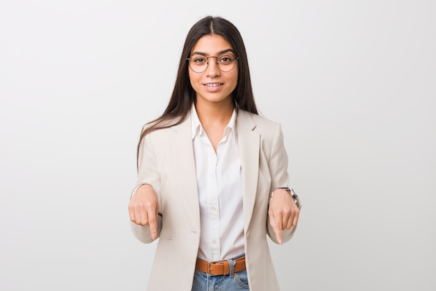Femme arabe jeune entreprise isolée contre un blanc pointe vers le bas avec les doigts, sentiment positif.