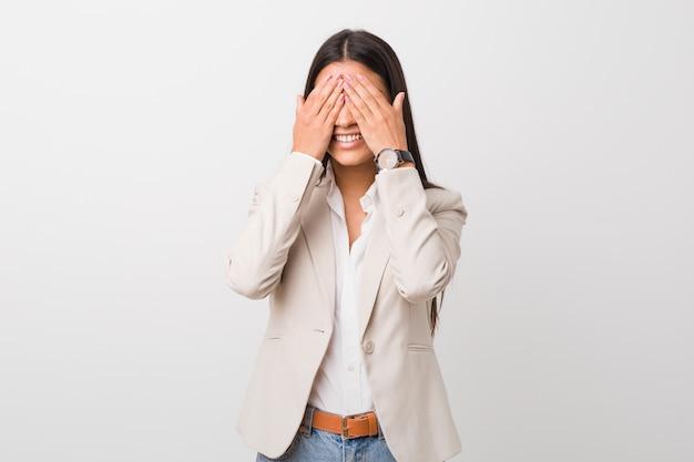 Femme arabe jeune entreprise isolée contre un mur blanc couvre les yeux avec les mains, sourit largement attendant une surprise.