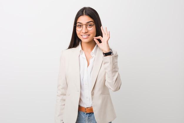 Femme arabe jeune entreprise isolée sur un fond blanc gai et confiant montrant le geste ok.