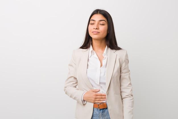 Femme arabe jeune entreprise touche le ventre, sourit doucement, concept de restauration et de satisfaction.