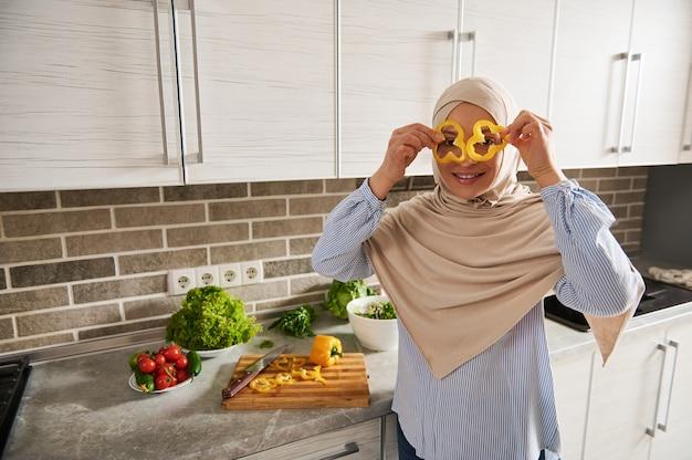 Femme arabe musulmane en hijab regarde à travers des tranches de poivron jaune, profitant de la préparation d'une salade végétalienne dans la cuisine