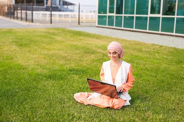 Femme arabe réussie et femme d'affaires arabe portant le hijab travaillant sur un ordinateur portable dans le parc
