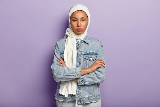 Une femme arabe sérieuse et sûre d'elle-même garde les mains croisées sur la poitrine, a une peau sombre et saine