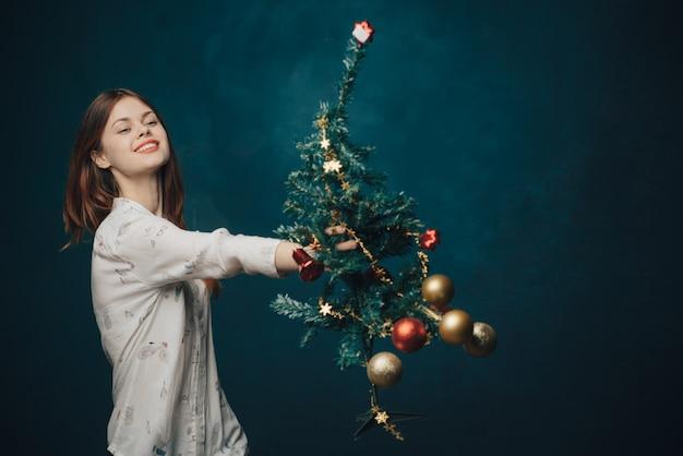 Femme avec un arbre festif sur un fond bleu boules de noël nouvel an. photo de haute qualité