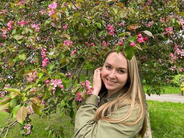 Une femme à un arbre en fleurs malus domestica spring girl au pommier