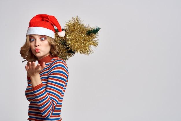 Femme avec un arbre de noël dans sa main cadeaux de chapeau de vacances clinquant jaune