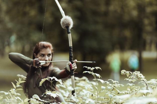 Femme archer tirant l'arc et la flèche dans le marais.