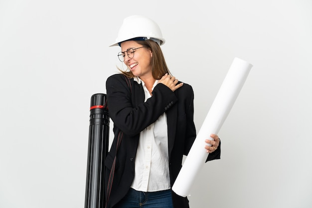 Femme d'architecte d'âge moyen avec casque et tenant des plans plus isolés souffrant de douleurs à l'épaule pour avoir fait un effort