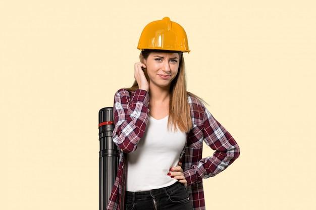 Femme architecte ayant des doutes sur un mur jaune isolé