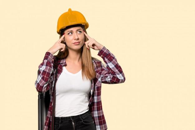 Femme architecte ayant des doutes et réfléchissant sur jaune isolé