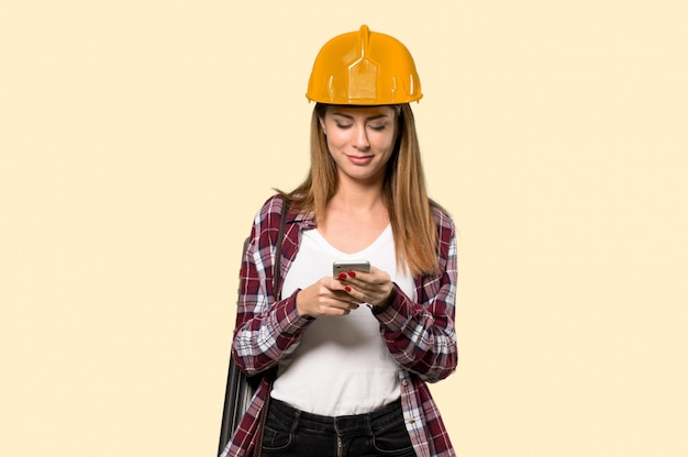 Femme architecte envoie un message avec le téléphone portable sur un mur jaune isolé
