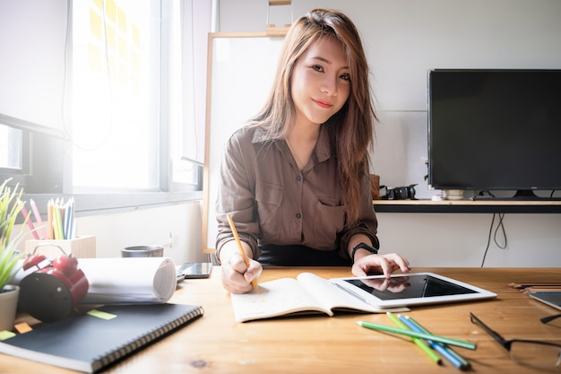 Femme architecte esquisse sur ordinateur portable au studio de design.