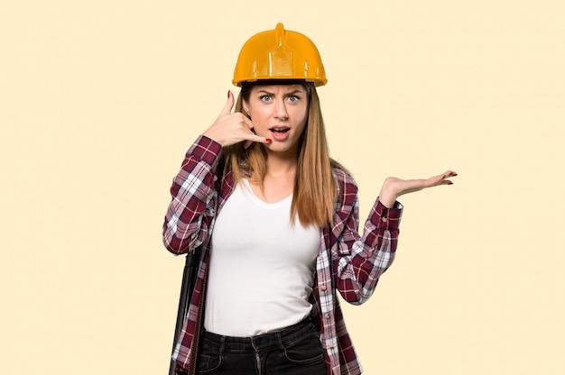 Femme architecte faisant un geste de téléphone et doutant d'un mur jaune isolé