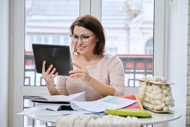 Femme architecte d'intérieur travaillant à table au bureau avec des échantillons de tissus décoratifs intérieurs pour rideaux, tissus d'ameublement, accessoires