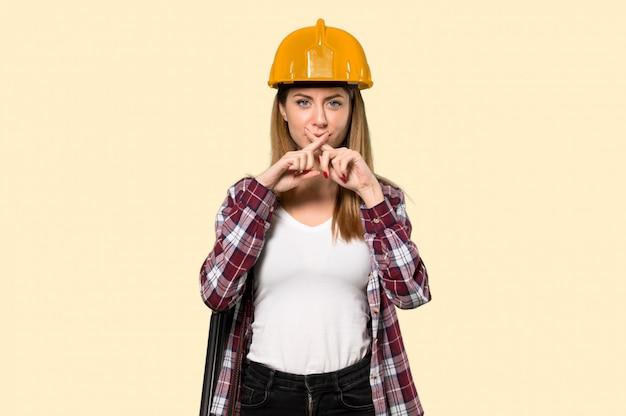Femme architecte montrant un geste du silence sur un mur jaune isolé