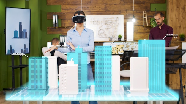 Une femme architecte portant un casque vr regarde les projections holographiques de la construction d'une ville. elle réorganise les étages d'une tour d'affaires