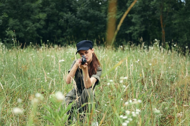 Femme avec une arme visant vers l'avant sur des squats sur des feuilles vertes en plein air