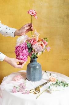 Femme arrangeant des fleurs dans un vase