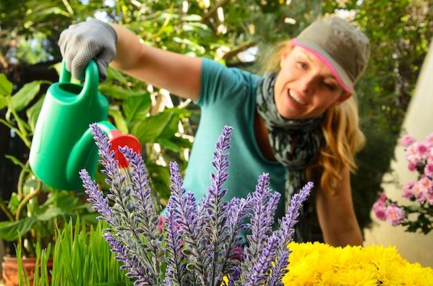 Femme arrosant le jardin botanique