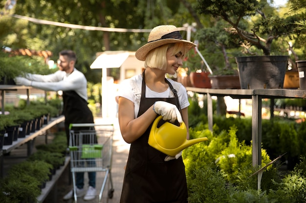 Femme arrosant les plantes coup moyen