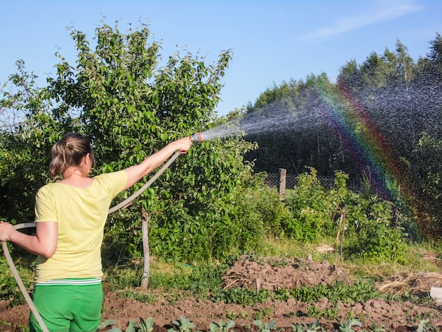 Une femme arrose un jardin et un arc-en-ciel s'est formé dans les embruns du soleil.