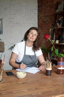 Femme artisanale écrit dans le cahier et la planification