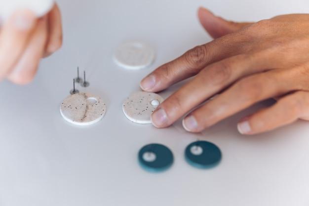 Femme artisanale sans visage fabriquant des boucles d'oreilles faites à la main à la maison.