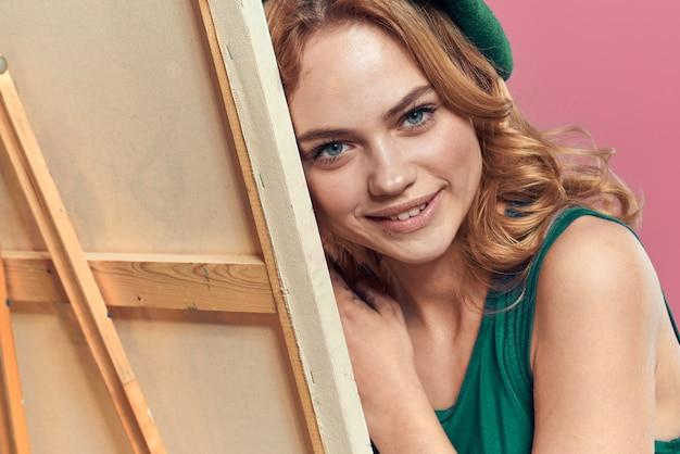 Femme artiste béret vert chevalet brosse cours de dessin art espace rose.